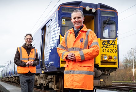 Hydrotrain 011: Image shows, Michael Matheson MSP - Cabinet Secretary for Transport, Infrastructure and Connectivity (orange jacket) photographed with Dr. Ben Todd, CEO of Arcola Energy (hi-viz waistcoat) and a 314 Class electric train at the Scotrail Depot in Yoker, Glasgow