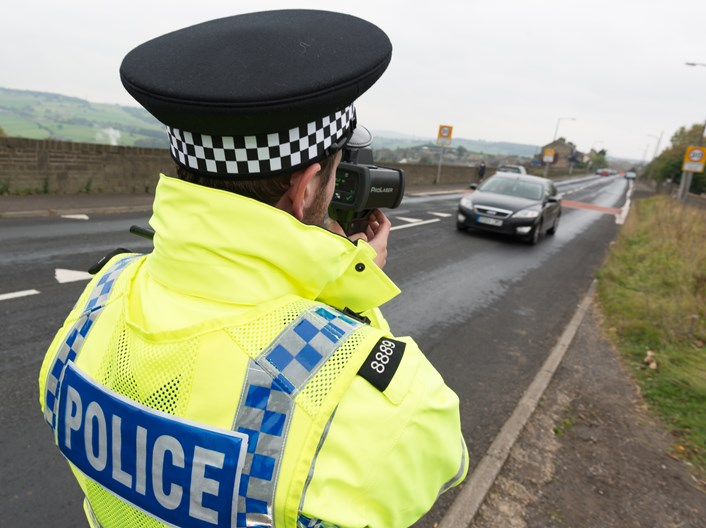 Police officer with handheld speed camera: Traffic police offer with handheld speed camera.  Image courtesy of West Yorkshire police.