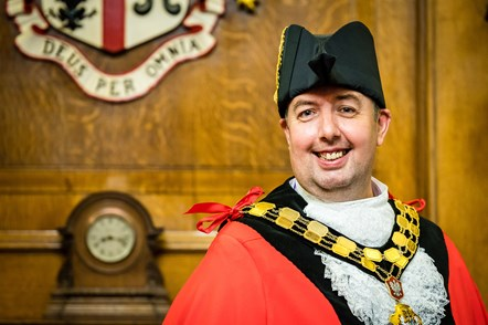 Cllr Troy Gallagher, Mayor of Islington for 2021-2022: A picture of Cllr Troy Gallagher in Mayoral Robes standing in the Mayor's Parlour in Islington Town Hall in front of the borough crest