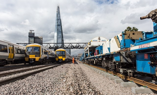 London Bridge - track laying in September 2017: Three Southeastern trains pass the Balfour Beatty track laying train in the shadow of the Shard outside London Bridge