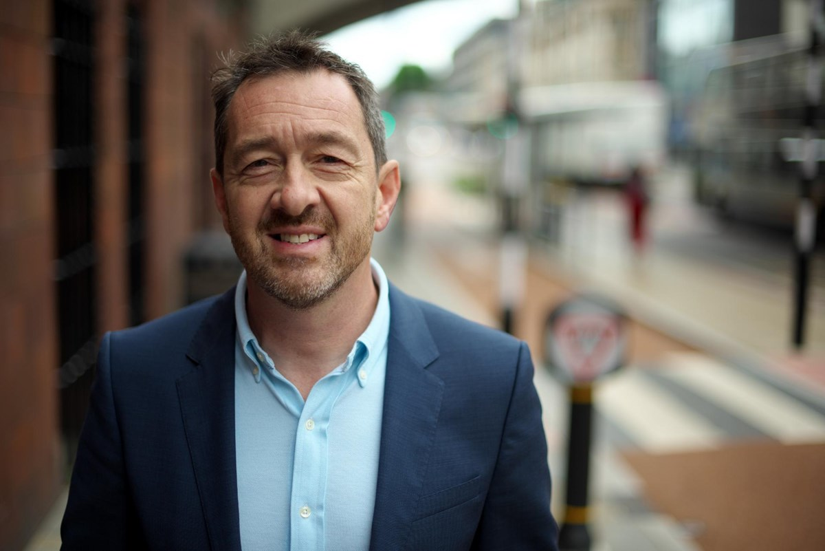 Headshot of Chris Boardman, GM Cycling and Walking Commissioner: Headshot of Chris Boardman, GM Cycling and Walking Commissioner, in front of blurred cycle lane, on Oxford Road, Manchester city centre