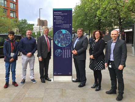 Greater Manchester wayfinding sign near to Piccadilly Bus Station: From left to right: TfGM Trainee – Sherez Ali, Trueform Engineering Ltd Northern Contracts Manager – David Gowans, TfGM Customer Director – Stephen Rhodes, TfGM Committee Member – Councillor Mark Aldred, Weston Williamson + Partners and Spaceagency Senior Associate – Kirsten Galea, TfGM Project Manager – Rene Guenther