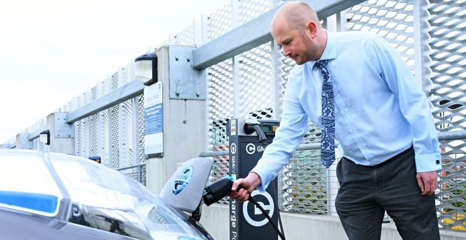 Businessperson charging electric car: Businessperson charging electric car using Greater Manchester Electric Vehicle (GMEV)  network charging point.