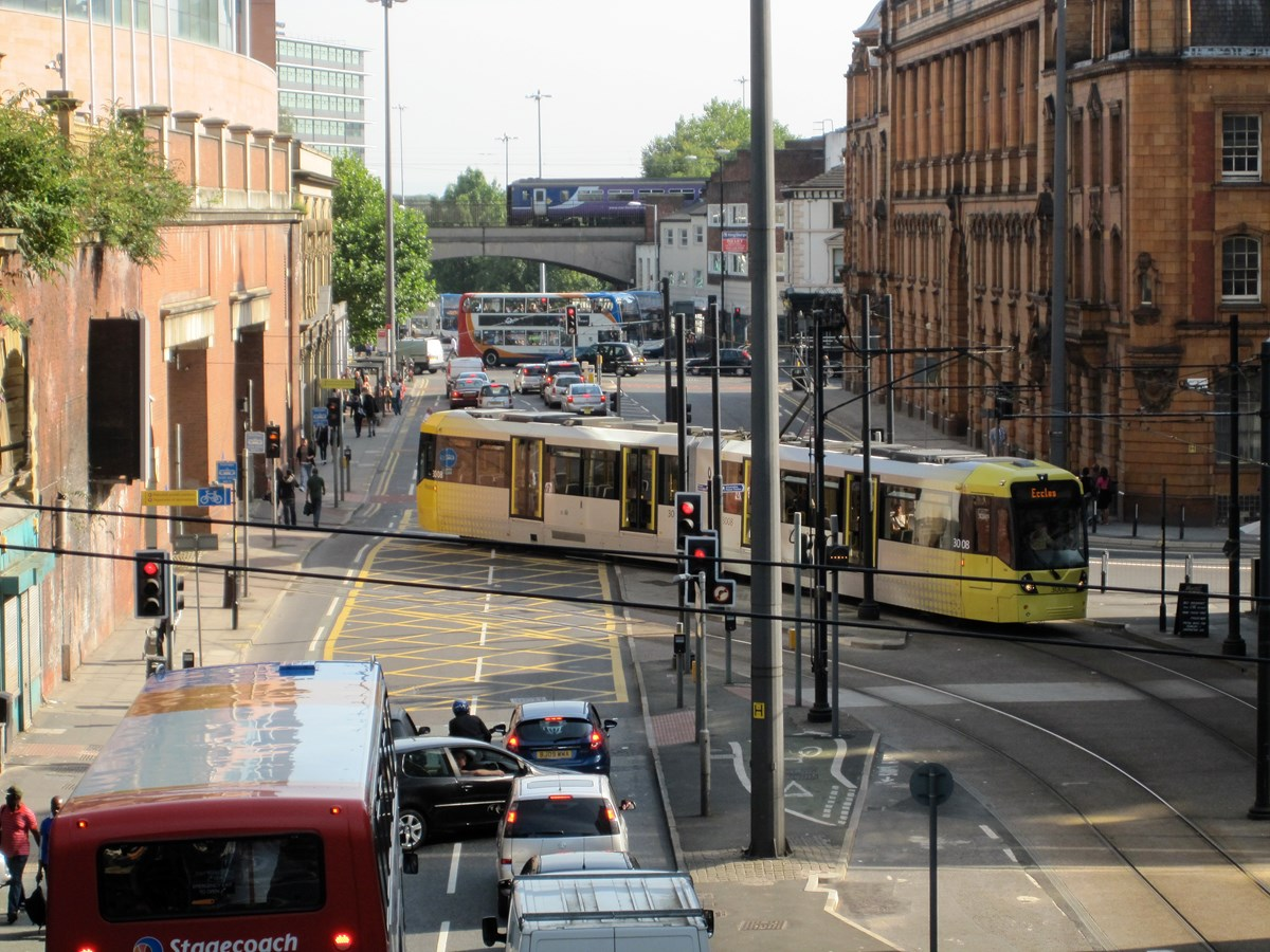 London Road traffic image: Picture showing traffic on London Road as well as four kinds of transport - car, bus heavy rail and tram.