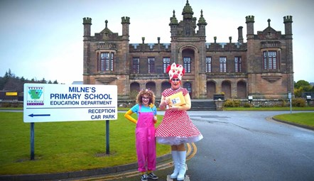 Out of the Darkness Theatre Company's Dame Deanie and Fairy Firth outside Milne's Primary School with DVD