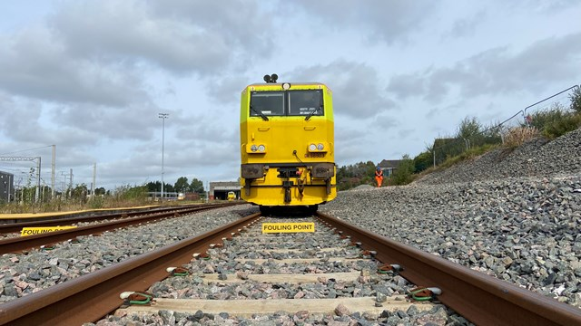 Track level view of autumn treatment train in sidings at Wigan