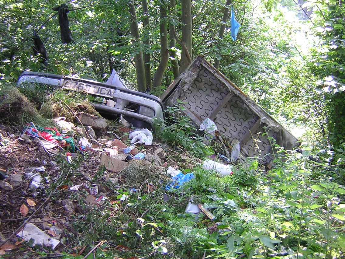 Fly-tipping - Surbiton, Surrey: An example of amount of rubbish dumped on railway land.   Location: behind a disused pub, Surbiton, Surrey. Photo taken June 2006