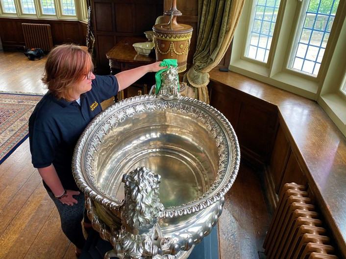 Silver wine cooler: Temple Newsam visitor assistant Rebecca Allott polishes the house's spectacular giant silver wine cooler ready to welcome visitors.
