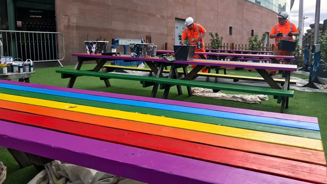 Network Rail workers painting the benches for Manchester Pride