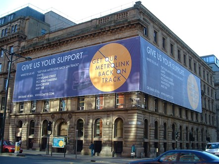 GMPTE Head Office Metrolink wrap: GMPTE Head Office, 9 Portland Street, M1, with Get Metrolink Back on Track wrap