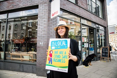 Esther Phelpotts, shop manager at Crisis in Stroud Green Road, Finsbury Park, promoting the Covid-Safe Business Award scheme window stickers