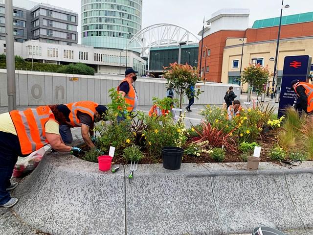 Volunteers working on Birmingham New Street's flower planters June 2021