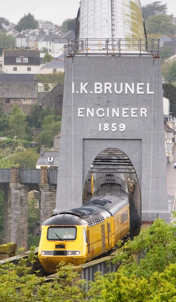 Royal Albert Bridge - unveiling Brunel's name: Portrait shot of Isambard Brunel's Royal Albert Bridge with Network Rail New Measurement Train passing through it.
