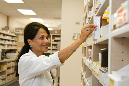 Photo of a female pharmacist selecting medicine from a shelf - Copyright free image by National Cancer Institute