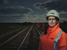Rebecca Grogan, mobile operations manager: Rebecca Grogan, one of our Orange Army female/woman mobile operations manager (MOM)  Engineers can be seen on track in the background  Rebecca is working over Easter bank holiday on our Railway Upgrade Plan