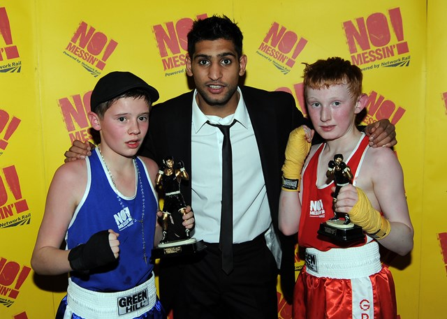 Portsmouth's Jack Featherstone (blue) and Lochaber's James Aitchison (red) collect their trophies from champion boxer Amir Khan at the No messin' tri-nation boxing competition