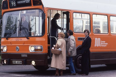 Passengers boarding Greater Manchester Transport number 98 bus pictured in 1981: A woman and two men about to board a single decker orange liveried Greater Manchester Transport bus, while a man in the door way clips his Clippercard. Bus destination blind reads number 98, Manchester Stevenson Square.