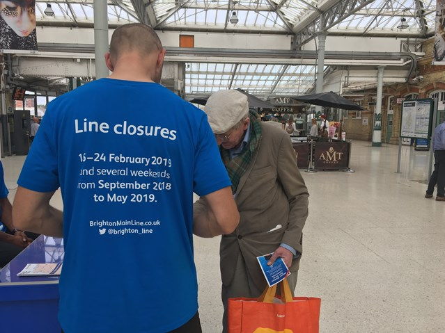 Passengers reminded to check ahead for weekend closures on the Brighton Main Line in October: Passenger picking up information at Eastbourne station about the line closures