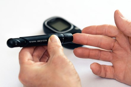 Diabetes blood check: Person checking own blood sugar levels with pin prick test