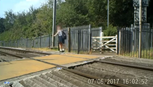 Young girl balancing on rail at Cotton Lane level crossing in St Albans