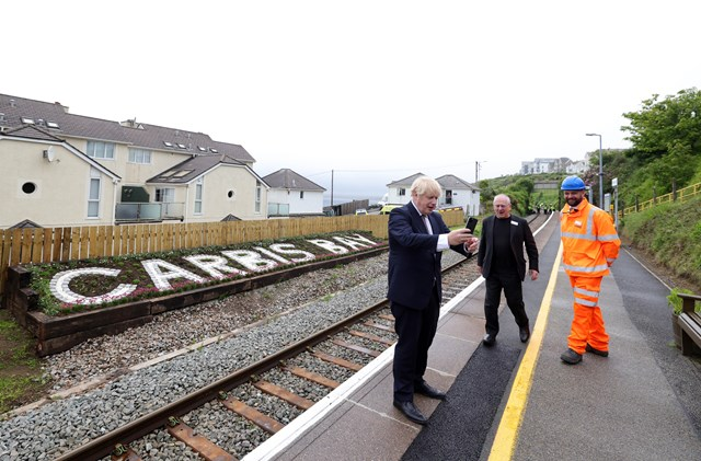 Prime Minister, Boris Johnson, takes a selfie in front of the new station sign at Carbis Bay.