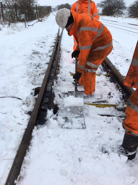 Passengers urged to check before they travel as snow and ice hits the north west: Clearing snow from a set of points