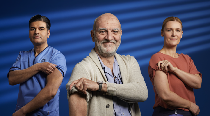 Two men and a woman with their sleeves rolled up to get a vaccine.