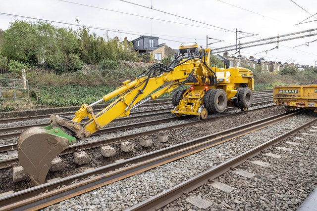 Digger removing old ballast during Willesden track upgrades March 2021
