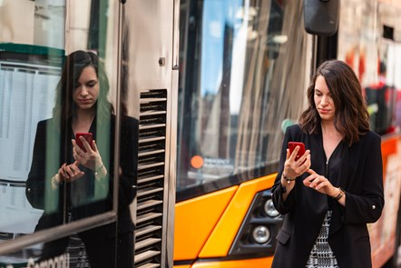 Passenger using phone at bus stop