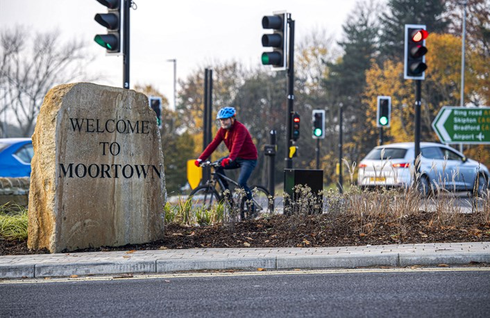 Person cycling past Welcome to Moortown sign