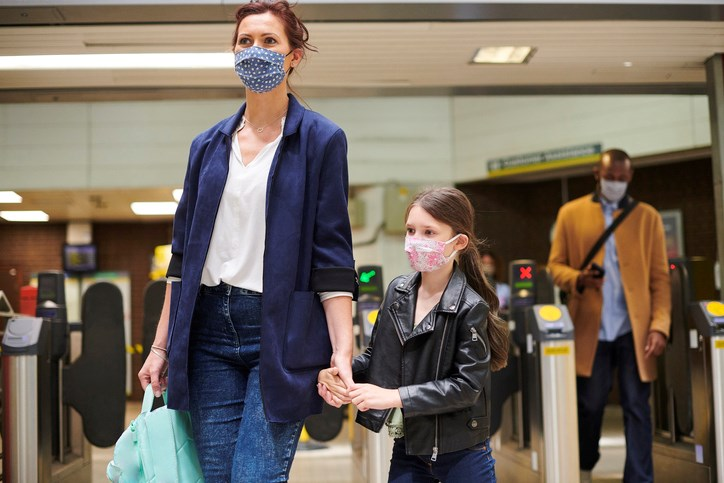 woman and child at station face coverings GettyImages-1257548238