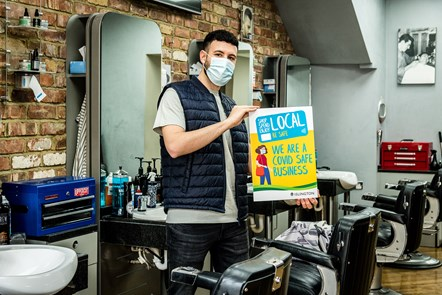 Pas Bertolino, of Stasi Barbers & Academy in Junction Road, Archway, promoting the Covid-Safe Business Award scheme window stickers