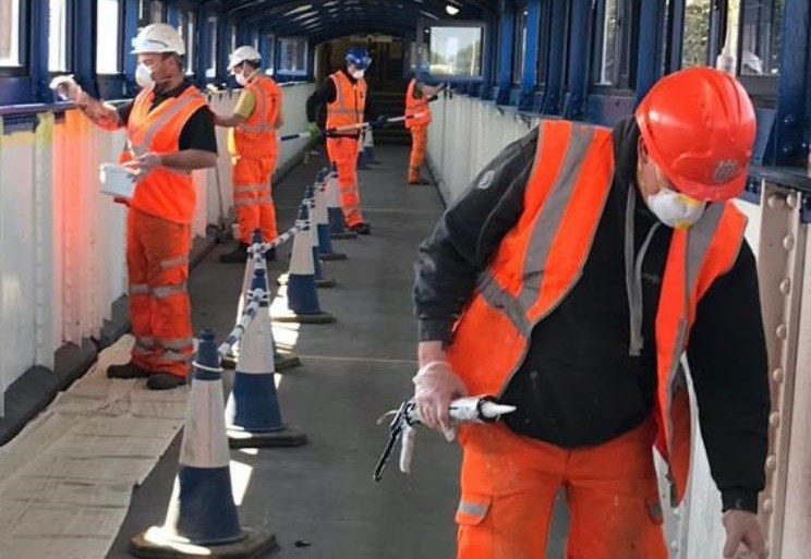 """Over £1.8 billion spent across the south on improvements with passengers returning to the railway more than 18 months after the first lockdown, Network Rail's Wessex route says """"welcome back"""": Social distancing while painting Guildford footbridge!"""