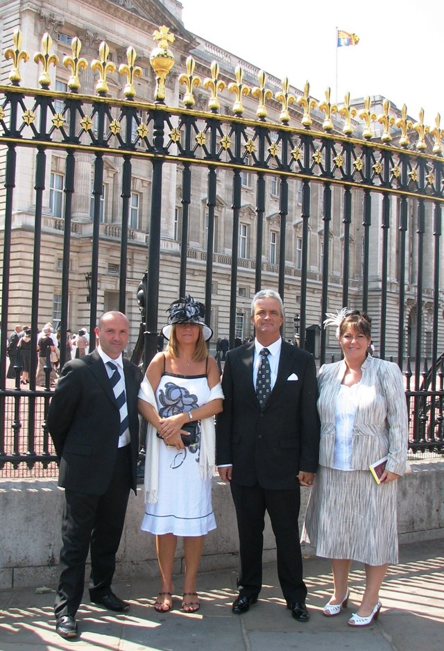 King's Cross Staff honoured at Buckingham Palace for 7/7 efforts: King's Cross Station Manager Peter Armstrong-Cribb (left) and Duty Station Manager Paul Chippington (right centre) with partners outside Buckingham Palace where they were honoured for their efforts during the 7/7 tragedy last year.