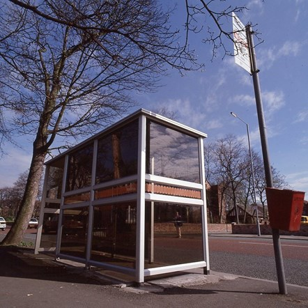 GMPTE bus shelter and stop: A GMPTE branded bus shelter with a tree behind and bus stop pole and plate alongside