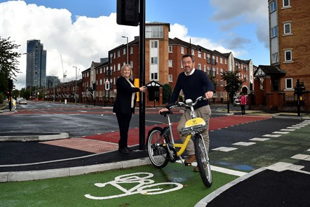 CYCLOPS launch Hulme-4: Wider shot of Manchester City Council's Executive Member for Environment, Councillor Tracey Rawlins and Greater Manchester Transport Commissioner, Chris Boardman, using the new CYCLOPS junction in Hulme. Chris Boardman is holding a branded Bee bike.