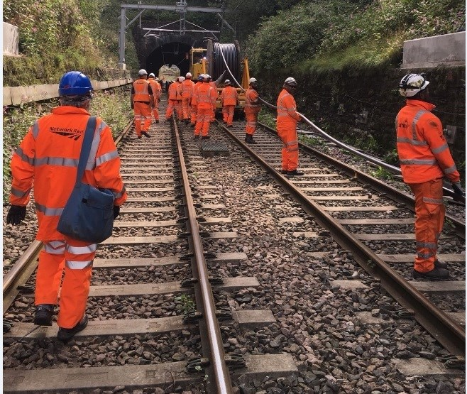 Train services resume on the Preston-Bolton-Manchester railway as upgrade nears completion: Team Orange installing power cables to supply new overhead equipment with electricity