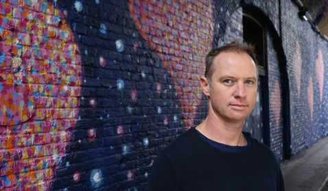 Jimmy C  poses with his artwork in Southwark