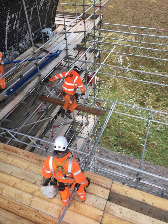 Network Rail teams on scaffolding platform working on underside of Ribblehead viaduct