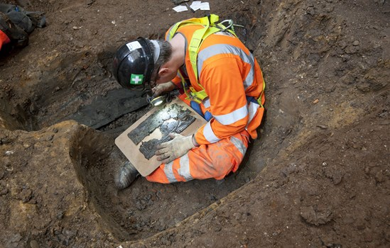 An archaeologist examines at coffin plate at St James's November 2018: Credit: MOLA Headland (Archaeology, launch, St James Gardens, people, jobs) Internal Asset No. 159