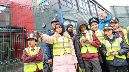 Students with Chris Boardman on 2019 Clean Air Day: A group of students wearing hi-vis jackets pictured in from of Webster Primary School with Cycling and Walking Commissioner Chris Boardman, on Clean Air Day 2019