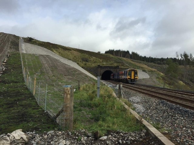 A Northern train travels along the Settle and Carlisle line past the drainage work at Dent, Cumbria