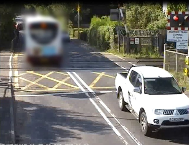 Yapton - level crossing: A bus races the red lights at Yapton level crossing, Sussex, and gets nabbed by the red light cam