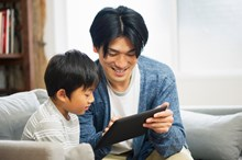 father-and-son-working-on-tablet-computer-at-home large