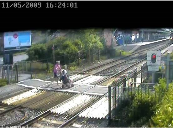 Mother dashes over crossing with baby in pram, Wareham, Dorset