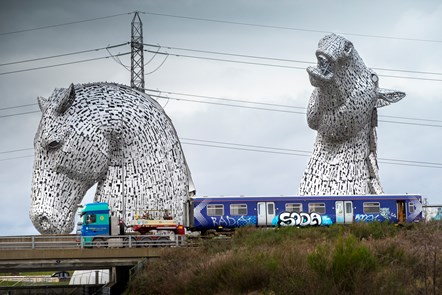 Hydrotrain 064: Image of Scotrail carriage loaded onto a truck, on its way to Bo-Ness, travelling past The Kelpies at Grangemouth, Forth & Clyde Canal on 18th Dec 2020. The train has been decommissioned and will be taken to Bo'ness where it will be converted to run on hydrogen.