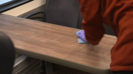 Cleaning train table on Greater Anglia service