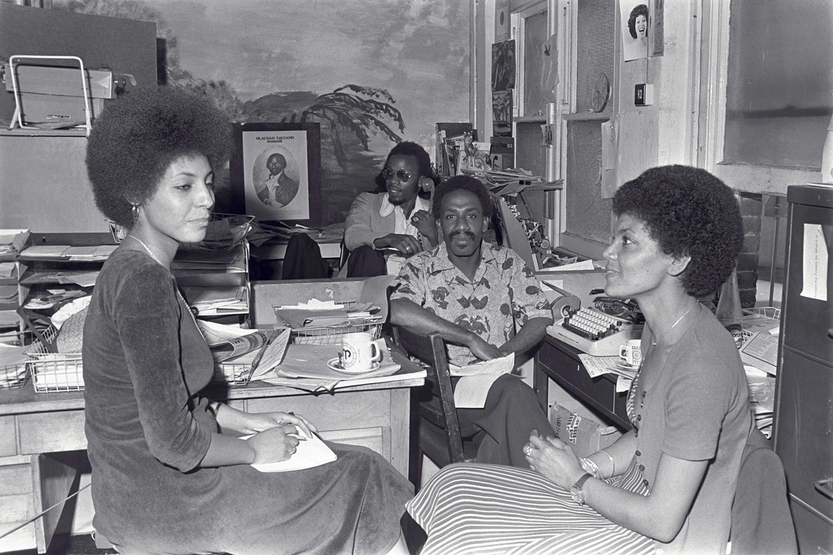 Tony Douglas, Russell Pierre, Leila Hassan and Barbara Bees: Caption: Tony Douglas (deputy editor) and Russell Pierre (editor) of the West Indian World, the first national black newspaper in the UK. They are interviewing journalist Leila Howe Hassan (left), member of the Black Unity, Freedom Party and editor of Race Today newspaper. She sits opposite her colleague Barbara Beese (right), who was one of the Mangrove Nine and member of the British Black Panthers. Islington, c.1974