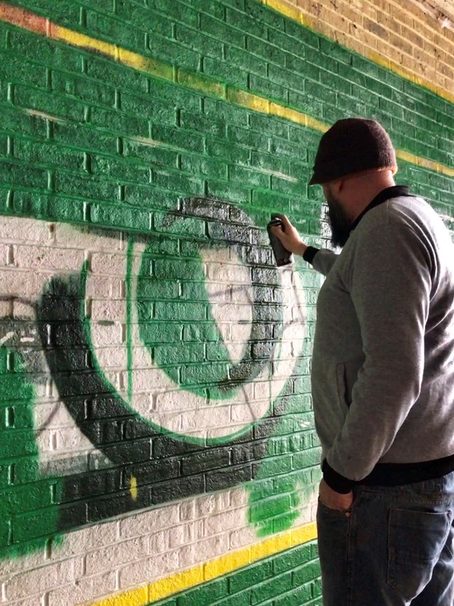 Lionel painting the mural on the passageway In Ashford.