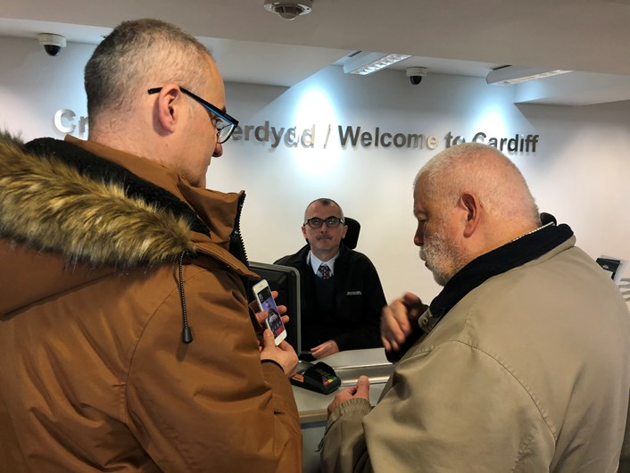 Jonathan Colligan from Interpreter Now shows Jonathan Bosman, of the deaf community how to use the app at Cardiff Central Booking office